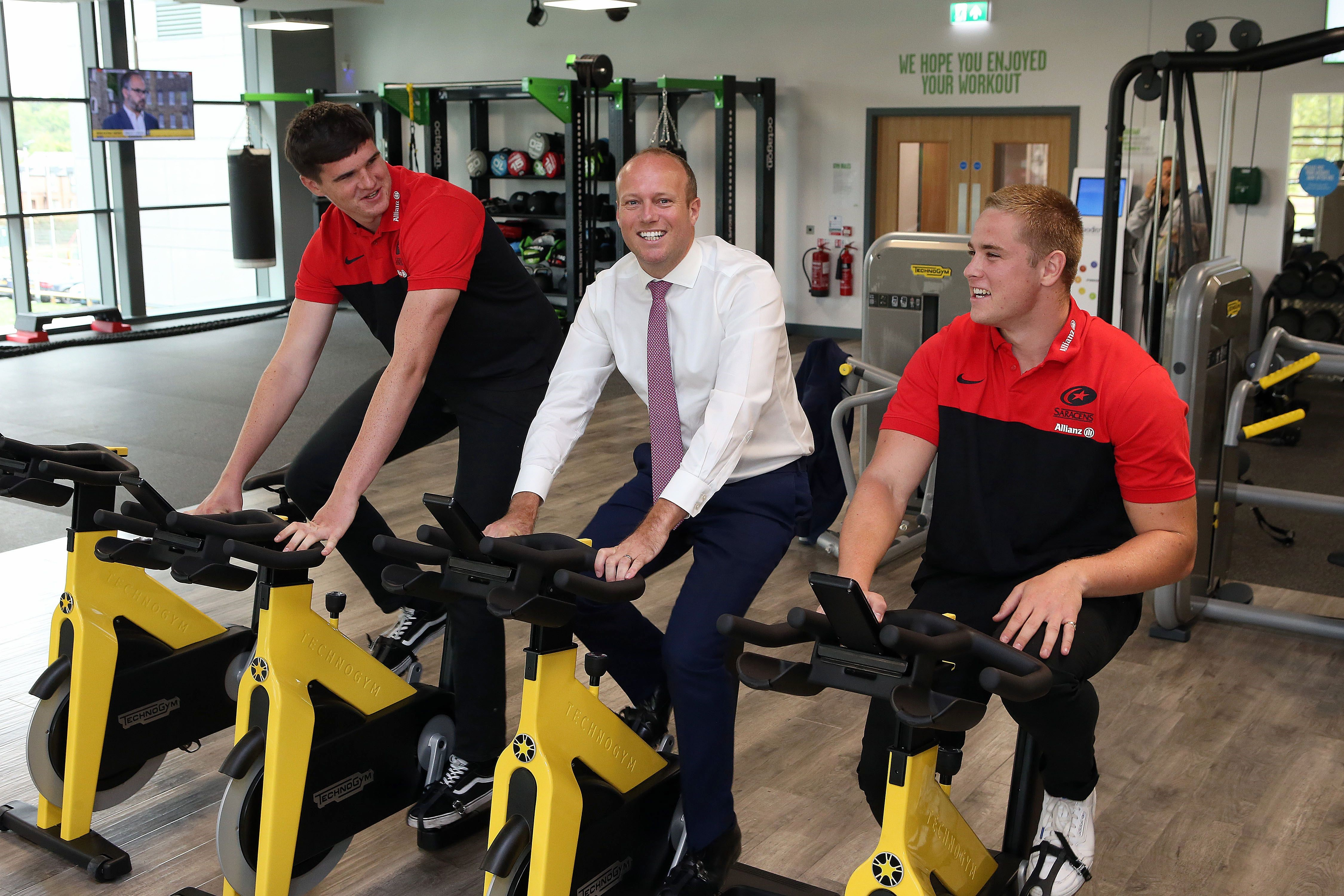 Leader of Barnet Council, Councillor Dan Thomas, with Saracens RFC players Cameron Boon (left) and Tobias Munday on the exercise bikes at New Barnet Leisure Centre.