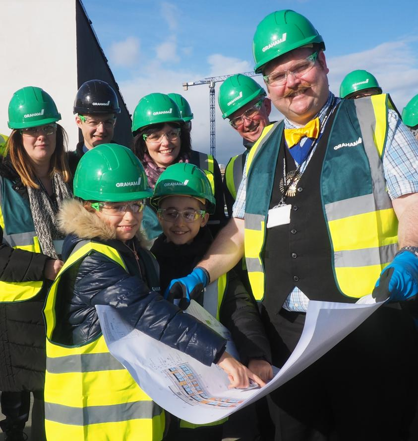 The Worshipful Mayor of Barnet, Councillor Reuben Thompstone, inspects the blueprint for the new building at its topping out ceremony