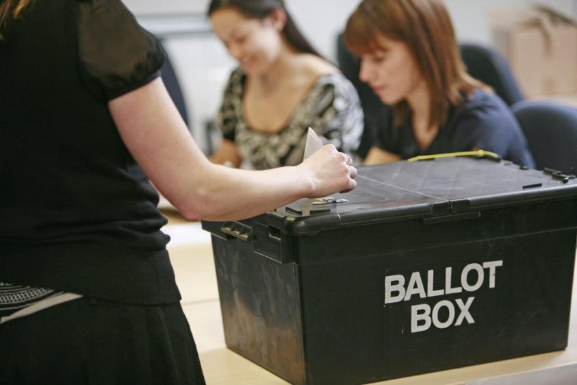 image of votes being cast in a ballot box
